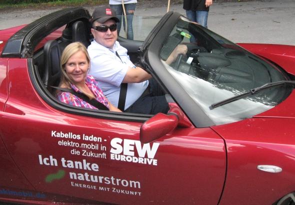 Ulrich Hopp läßt die Beschleunigung vom Tesla Antje van de Weyer spühren
